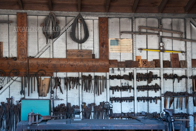 Harnesses, and tools hang on the wall of the blacksmith shop.