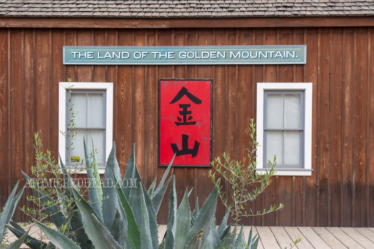 "Exterior of an unpainted wood building. A green sign reads ""The Land of the Golden Mountain"" a red sign below features Chinese characters."