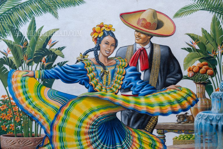 A couple in traditional Mexican fiesta attire is painted on an adobe wall.