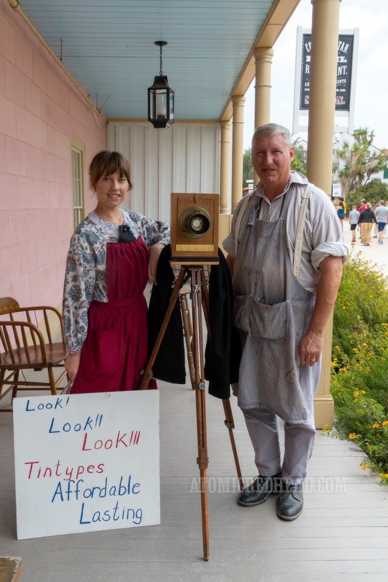 "Catherine and her father stand with their camera and a sign reading ""Look! Look!! Look!!! Tintypes Lasting Affordable"""
