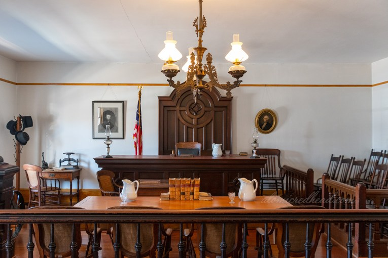 Interior of the courtroom, featuring dark wood seat for the judge, and table for defense and prosecution. An old fashioned brash lamp hangs from the ceiling.