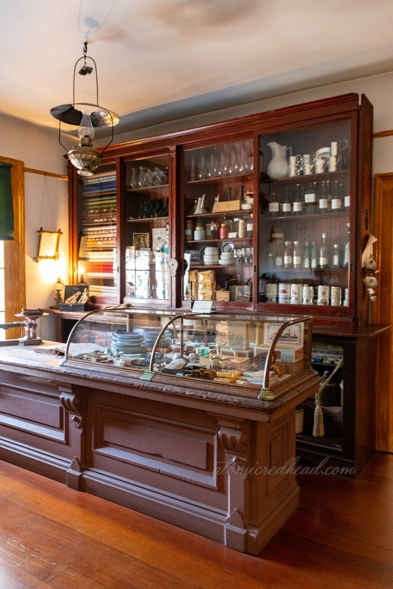 Area of the home that was Whaley's general store. Dark wood display cases feature various items from the era.