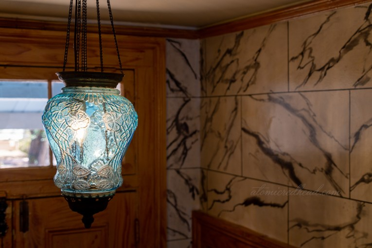 A blue glass light fixture featuring a floral motif hangs in the hallway.