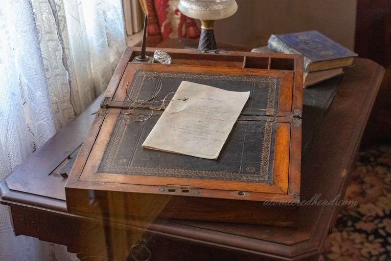 A portable writing desk sits atop a table, with a letter, and pair of glasses atop.