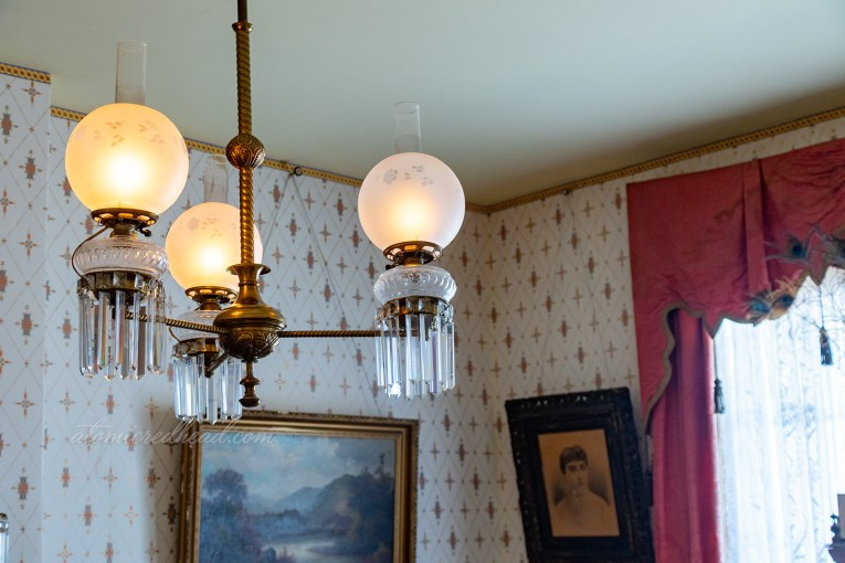 The light fixture of the parlor, three glass globes with crystals hanging below.