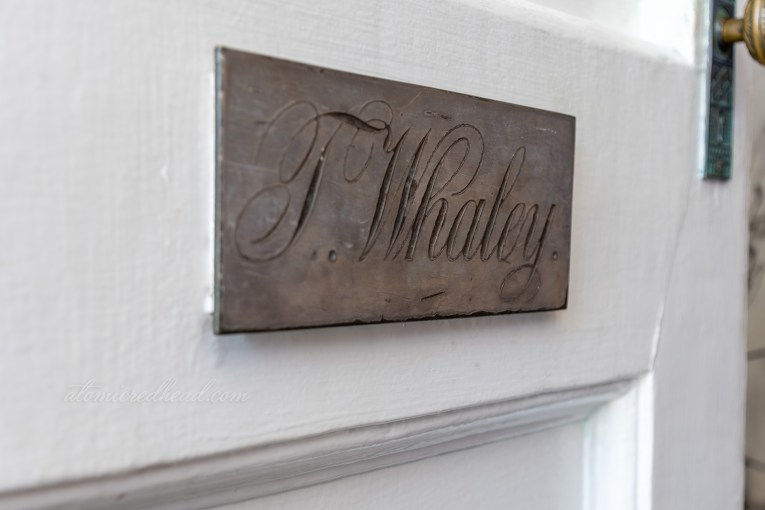 "A plaque reading ""T. Whaley"" is affixed to the front door."