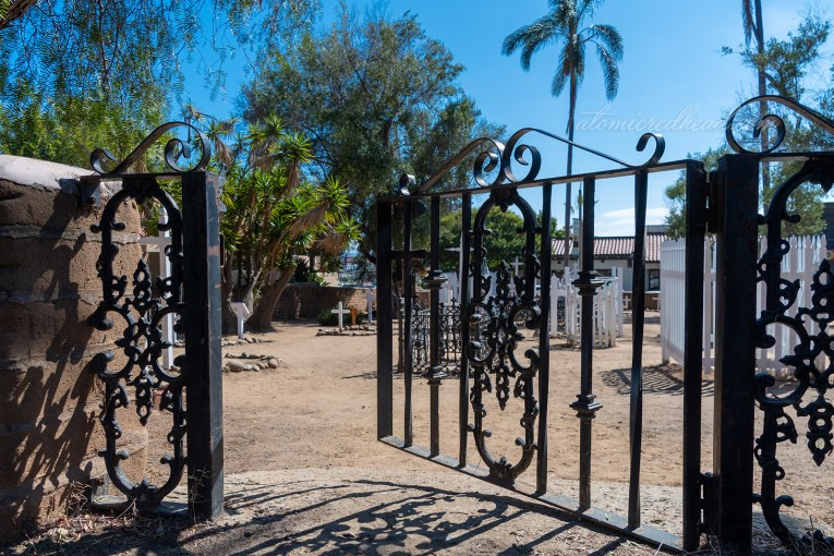 A black wrought iron gate opens into the cemetery.