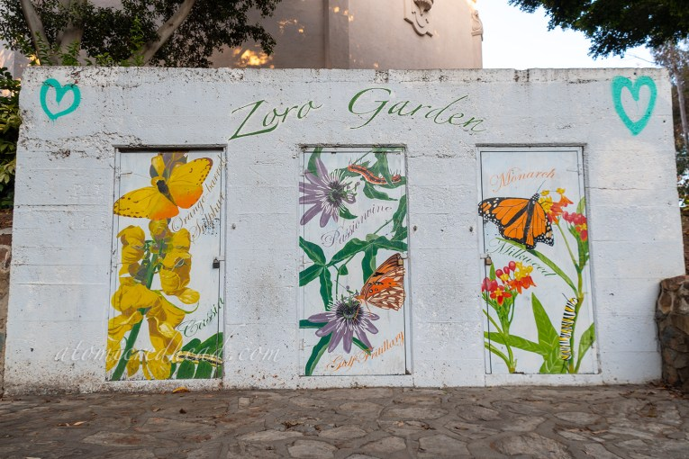 "A white building is painted with flowers and butterflies. Green text reads ""Zoro Garden"""