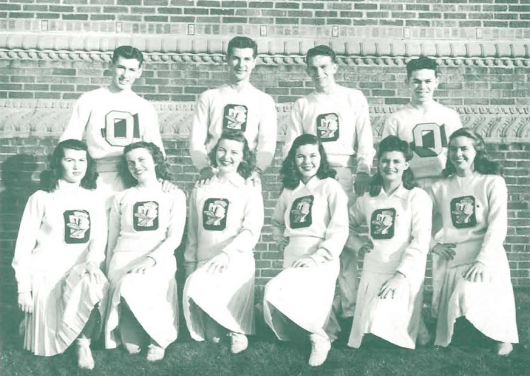 University of Oregon's Rally Squad, wearing white outfits, the ladies' sweaters feature a large O, with a Duck head in the middle.