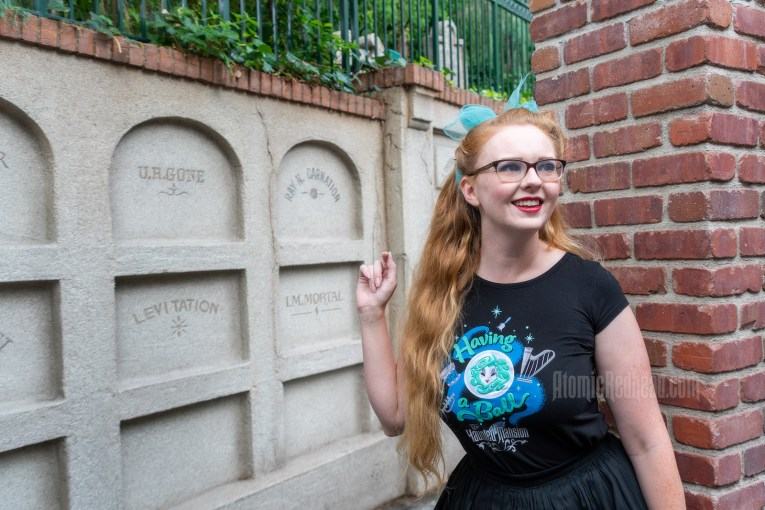 "Myself standing in front of a faux mausoleum at the Haunted Mansion, wearing a black t-shirt with Madam Leota (a medium with her head floating in a crystal ball) and music instruments floating about on it, reading ""Having a Ball"" and a black full skirt."