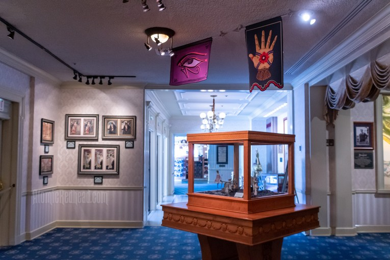 Overall image of the gallery, featuring concept art on the wall, a display case with small sculptures within, above hang two banners, one of the Eye of Ra, the other features a hand wrapped in ribbon with a rose in the center.