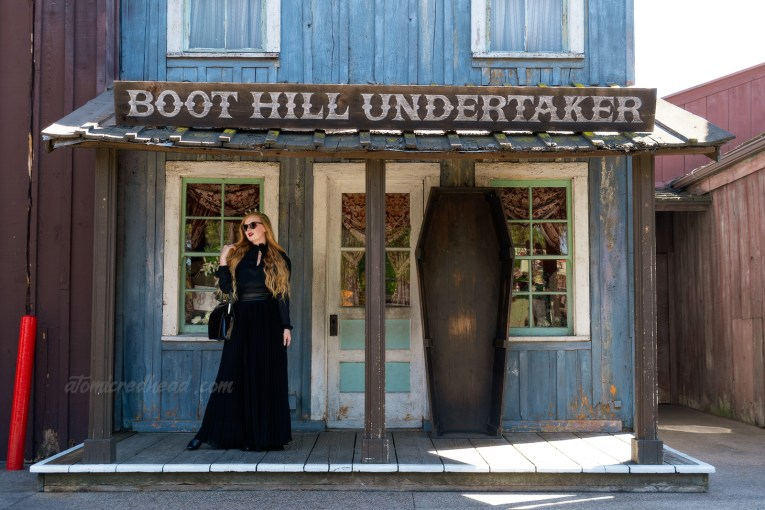 Myself, wearing a black long sleeve high collar blouse, and a long black skirt, holding a black coffin shaped purse, and a tiara made of small tombstones, standing in front the the Boot Hill Undertaker, a western style building with a coffin standing out front.