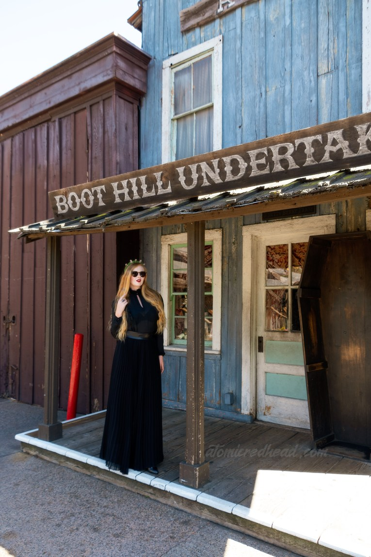 Myself, wearing a black long sleeve high collar blouse, and a long black skirt, and a tiara made of small tombstones, standing in front the the Boot Hill Undertaker, a western style building with a coffin standing out front.