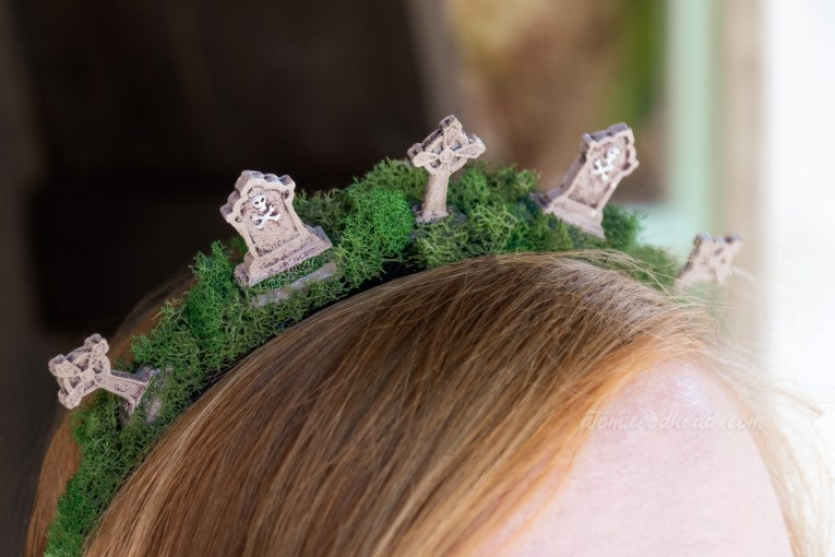 Close-up of my headband, which is covered in moss and made of mini tombstones to create a tiara like image.