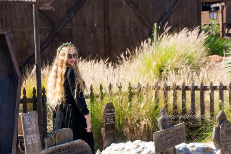 Myself, wearing a black long sleeve high collar blouse, and a long black skirt, holding a black coffin shaped purse, and a tiara made of small tombstones, walking through the Boot Hill cemetery, which features wooden tombstones.