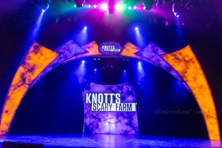 "The stage for the announcement for Knott's Scary Farm, lit in eerie orange and purple lights. Text reading ""Knott's Scary Farm"" in white letters is on a screen at the back of the stage and a small sig at the top of the stage."