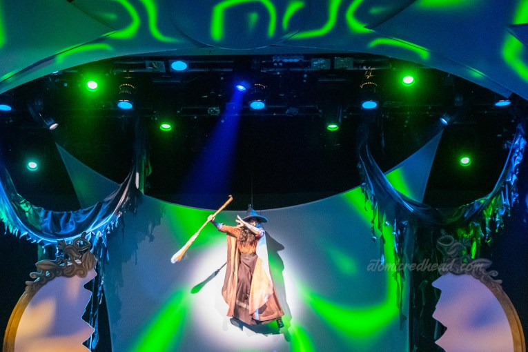 The Green Witch, also known as Sarah Marshall flies above the stage. She wears a long dress, with a billowing cape, a pointed witch hat and carries a broom.