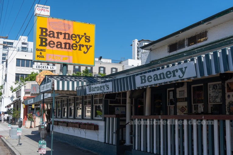 "Exterior of Barney's Beanery, a two story California Craftsman painted green and white, with an orange and yellow sign reading ""The Original Barney's Beanery Games & Pool"""