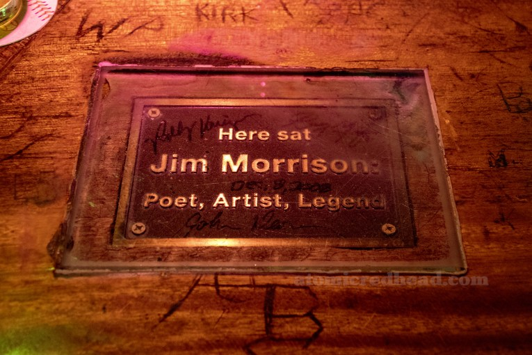 "A bronze plaque is embedded in the bar and reads ""Here sat Jim Morrison Poet, Artist, Legend"""
