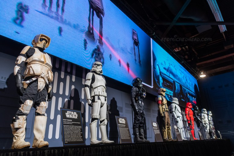 A row of various stormtrooper uniforms stand on a raised platform.
