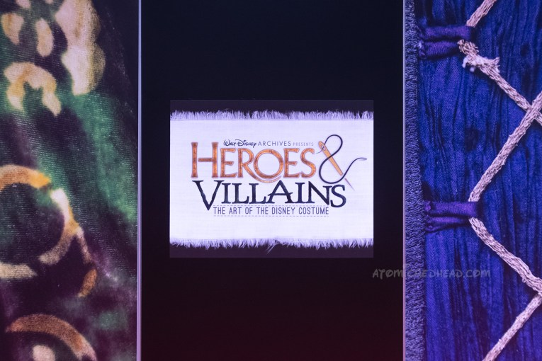 "Sign for the exhibit. Text reading ""Heroes & Villains"" appears as if it on a clothing label."