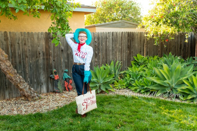 "Myself standing in our backyard, with lush agave plants, wearing a blue cowboy hat, blue gloves, red bandana, a white shirt with blue plaid and red text reading ""Frito Kid"" and blue jeans, and brown cowboy boots, holding a cream canvas bag reading ""Casa de Fritos"" is red script."