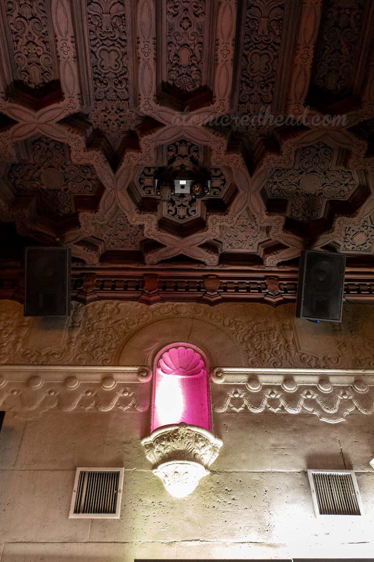 The elaborate carved wood ceiling, and almost cathedral like stone work with a lighted niche.