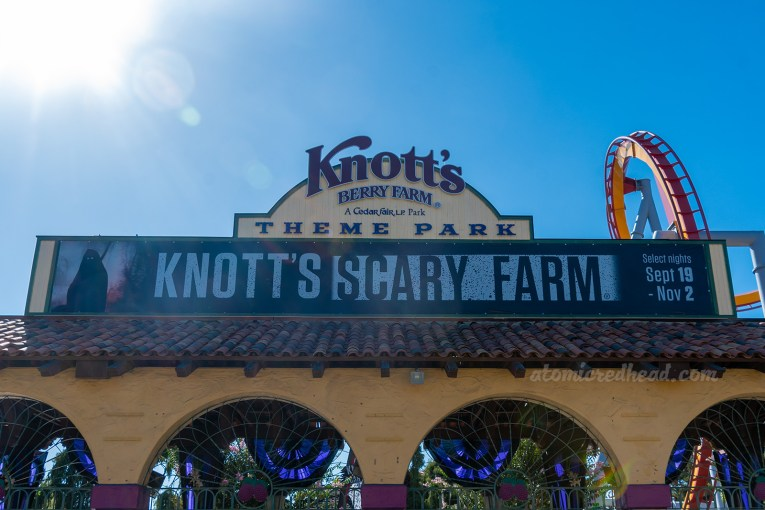 "Entrance to Knott's Berry Farm. A black and white banner reads ""Knott's Scary Farm"" above the arched gateways into the park."