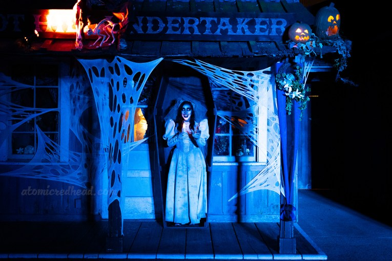 A ghostly bride stands inside a coffin on the porch of the undertaker's.