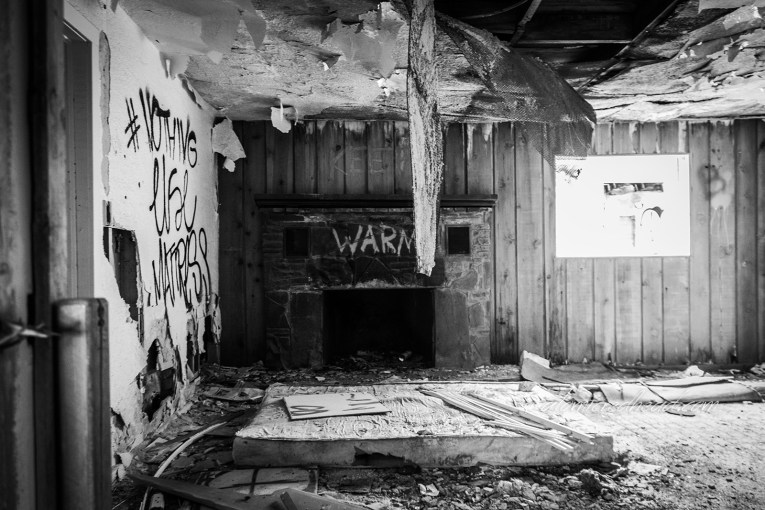 """Interior of the Twin Arrows Trading Post. A black and white photo. The ceiling is peeling away to reveal bare studs. A stone fireplace has had """"WARM"""" spray painted on the top of it. A mattress lays on the floor among other bits of debris."""