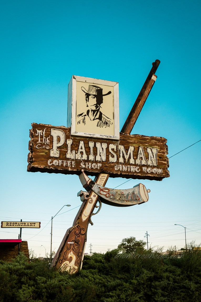 "Sign for the Plainsman Restaurant. A large metal and neon rifle juts up toward the sky. Across the middle of it a faux wood sign reading ""The Plainsman"" and a framed image of a cowboy is atop it."