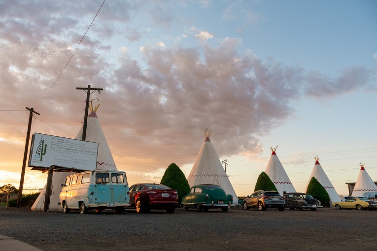 "Several of the ""cabins"" against a sunrise, with some clouds, all ""cabins"" are concrete tipis, several cars, including classic cars, are parked out front."