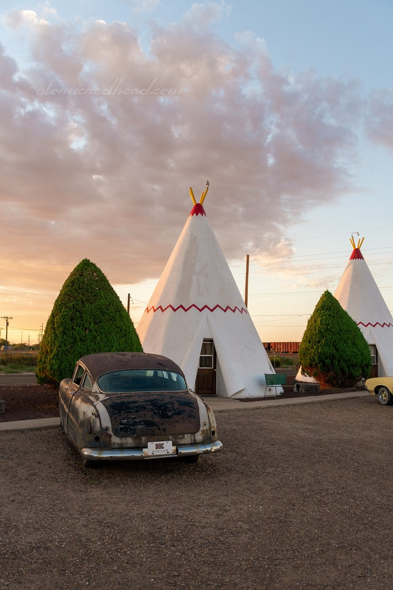 A 1940s car is parked in front of one of the tipis. The tipi is white with a red zig-zag across the middle.