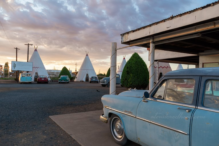 A pale blue Studebaker sits out front of the office, and in the background tipi cabins.