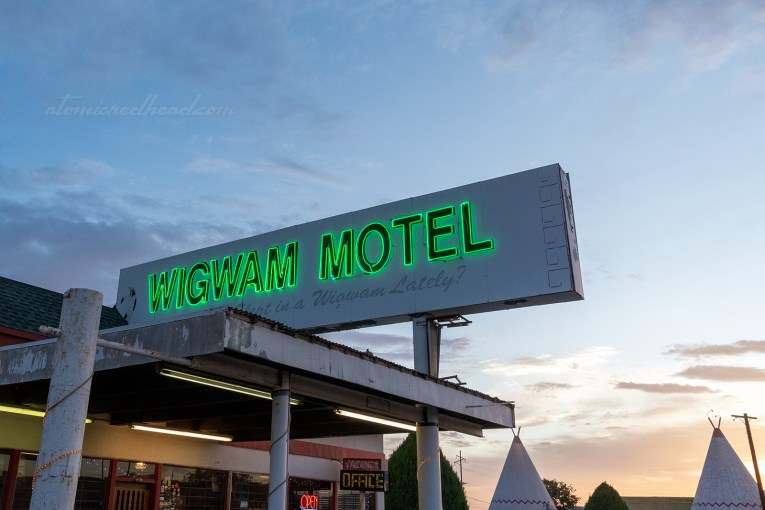 "A large white sign sits above the office, it reads ""Wigwam Motel"" in green neon letters."