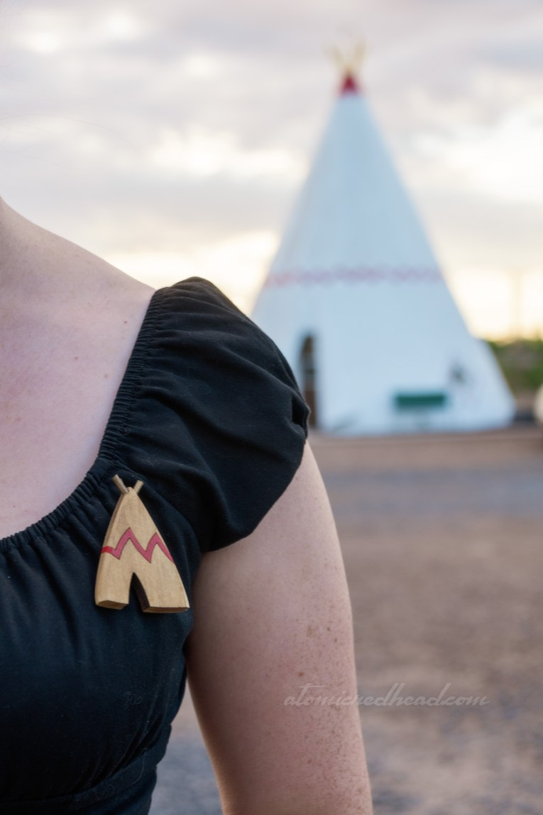 Close-up of my brooch, which is made of wood, and is a pale shade of tan, it features a red zig-zag across the middle. In the distance, just out of focus is one of the tipi cabins.