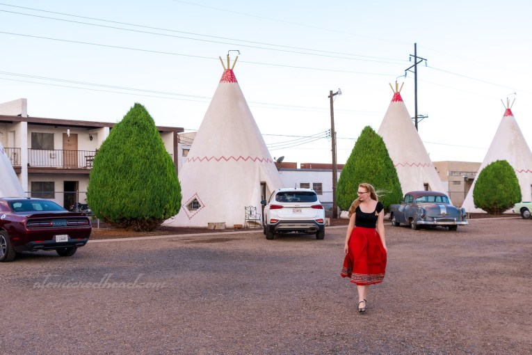 "Myself, standing in front of one of the ""cabins"" which is a concrete tipi, painted white with a red zig-zag horizontally across the middle. I'm wearing a black peasant top with a tipi brooch reflective of the ones at the motel, and a full red skirt with silver and black trim."