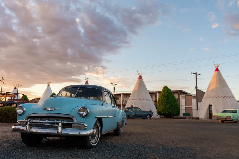 An early 1950s blue Chevy sits in front of some of the tipis. Clouds roll in over a blue sky as the sun rises.