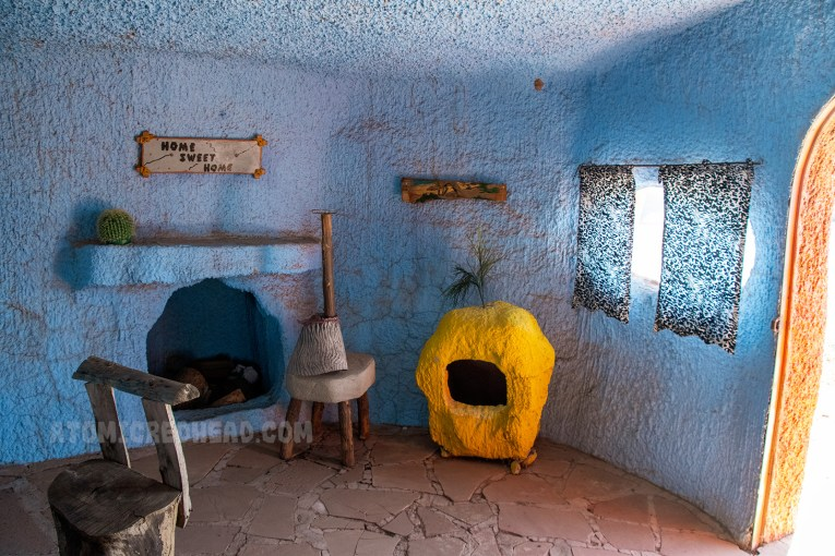 Inside Barney's house. Everything appears as if it were carved out of rock, but is really sculpted concrete. A fireplace is on the left, and a yellow TV on the right. The curtains are made from zebra print fabric.