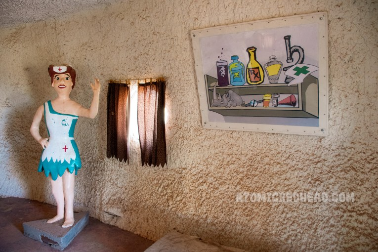 Inside the Medical Center, where a statue of a stone age nurse stands, wearing a teal dress with white apron. A painting on the wall of various bottles makes it appear like a cabinet.