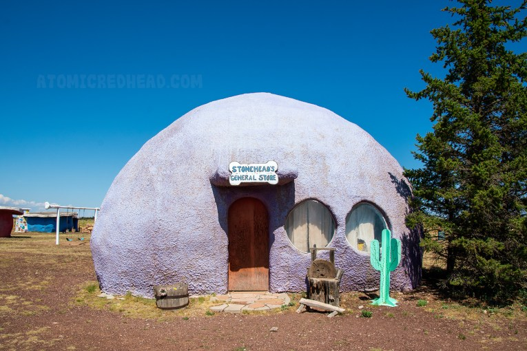 """""""Stonehead's General Store"""" a dome like building made of concrete, with round windows."""