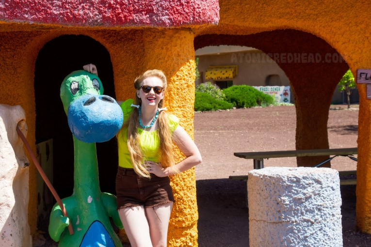 Myself wearing a lime green peasant and brown cut off shorts, leaning against the blue and green dino.