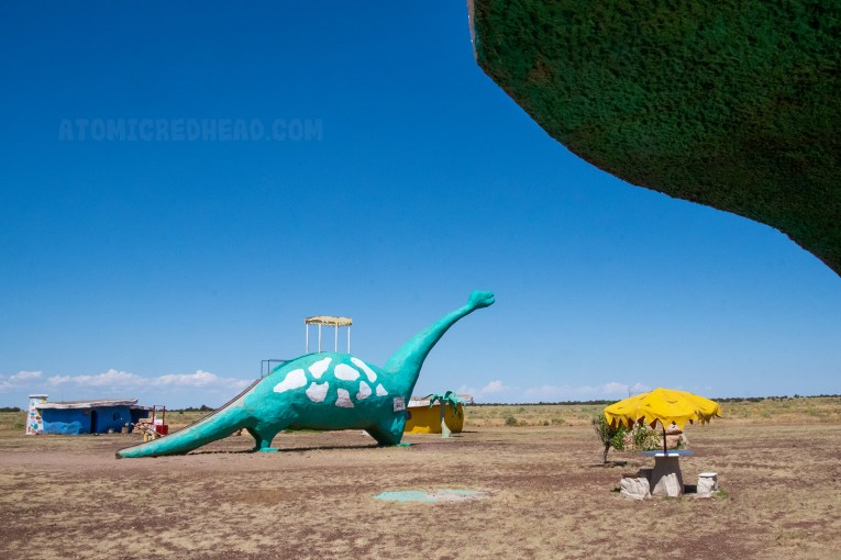 A massive long neck dinosaur stands in the middle of Bedrock. He is green with yellow spots. A small awning is in the middle of his back, and he is really a slide! Climb up just under his neck, and slide down his tail.