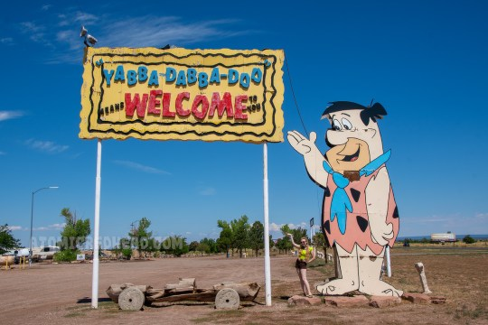 "A massive sign of Fred Flintstone and and sign reading ""Yabba Dabba Doo Means Welcome to You!"""