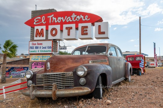 "The roadside sign for ""El Trovatore"" a brick structure stands on a hill above the motel, with a red and white sign jutting from the brick reading ""El Trovatore Motel"" An old rusted car sits out front."
