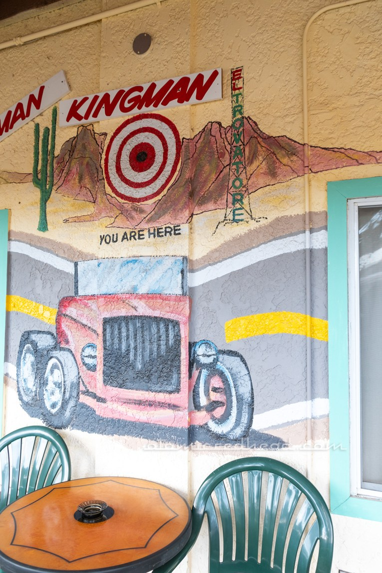"Part of the map mural, a hot rod sits under a target with text reading ""Kingman You Are Here"" and a painting of the El Trovatore tower."