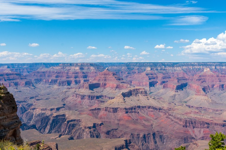 The Grand Canyon, as viewed from the south rim, a deep reddish-orange canyon, with layers creating stripes of various shades of red, brown, and tan. A blue sky is above with small fluffy white clouds.