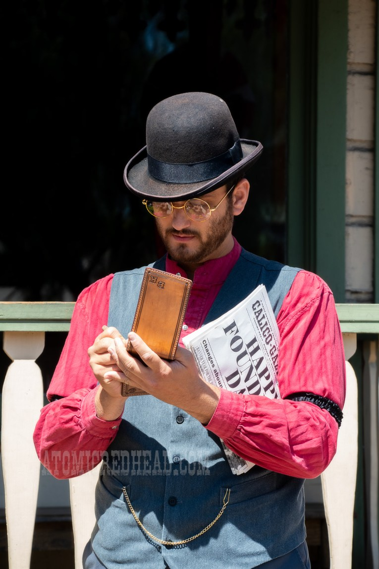 The Calico Gazette editor, Mr. Knolls, takes notes. He wears a red shirt with grey vest and black bowler hat.
