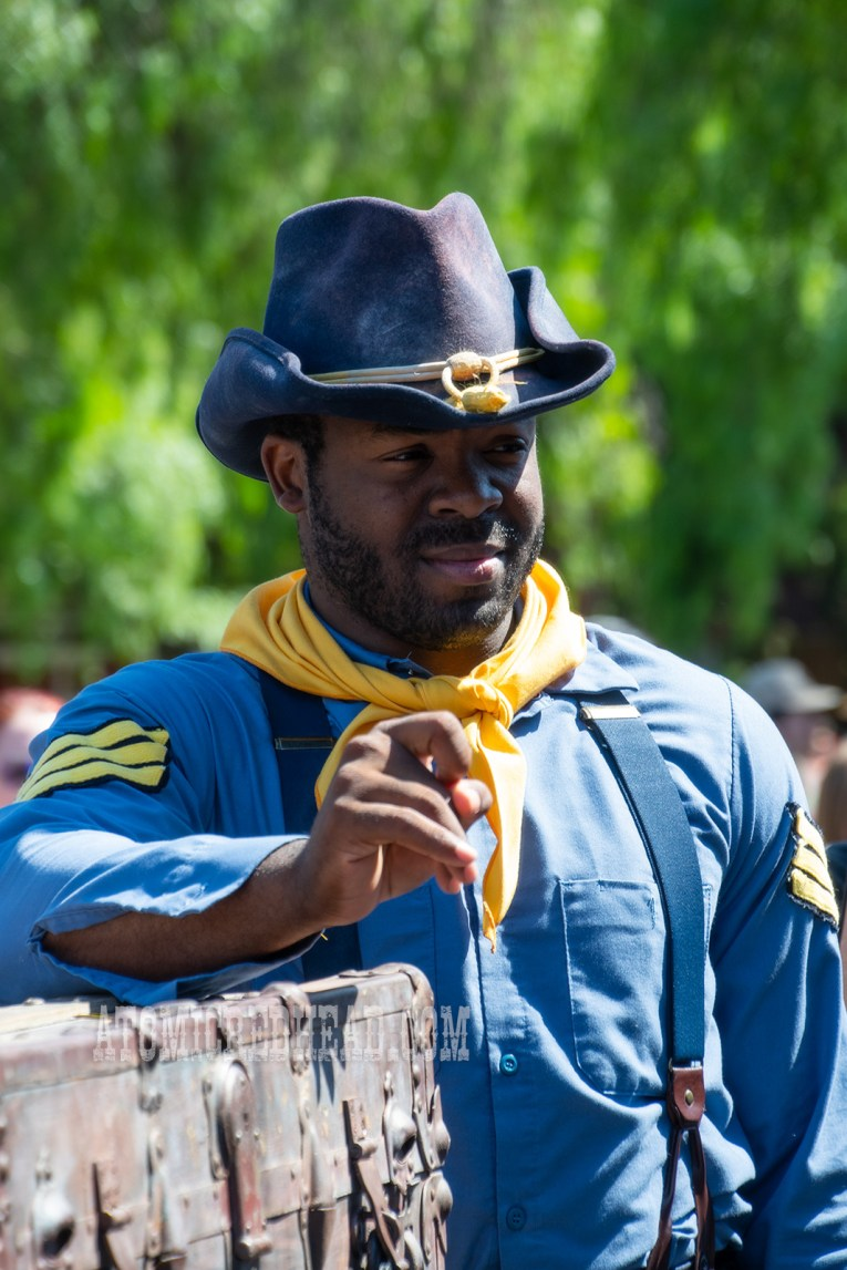Sargent of the Calvary, wearing a blue uniform with yellow bandana, rests against a large trunk.