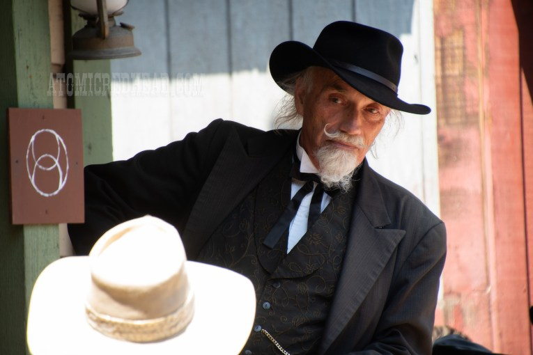 Judge Roy Bean, the town judge, wearing an ensemble of all black, with black string tie, listens to the accused.